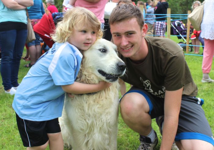 Kade Jameson gives Grissom a hug with Paul Kerins at the Dog Show in the Town Park on Saturday. Photo by Dermot Crean