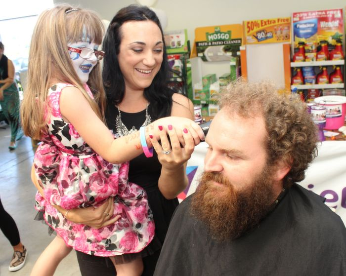 Daughter Erin makes the first shave to dad Paul, while Aoife McEllistrim looks on at the headshave in aid of the A-T Society in Woodies on Saturday. Photo by Dermot Crean
