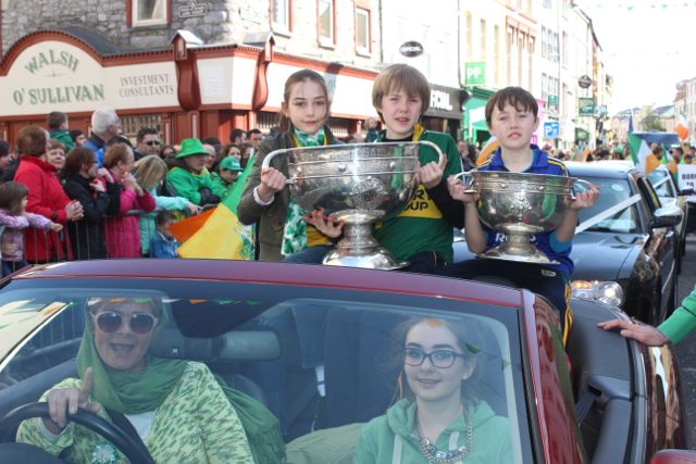 Olivia Wall drives the Sam Maguire and Tommy Markham cups with a little help from her friends at the parade. Photo by Dermot Crean
