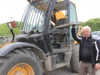Secretary of the Kerry District League, John O'Regan, next to a plank of wood which was thrown through the cab window of one of the machines by thieves. Photo by Gavin O'Connor.