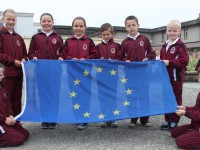 At the raising on their new blue flag were Moyderwell National School pupils, from left: Lilly O'Brien, Sara Peterniece, Isabella Moloney, Grace McCannon, Kevin Gaxa, Gerard O'Shea, Endijas Maurinns and Luke Enright. Photo by Gavin O'Connor.