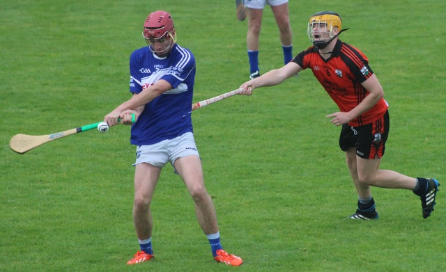 Ballyheigue's, Paudie Carroll, attempts to hook, St Brendan's, Fionan Mackessy. Photo by Gvain O'Connor.