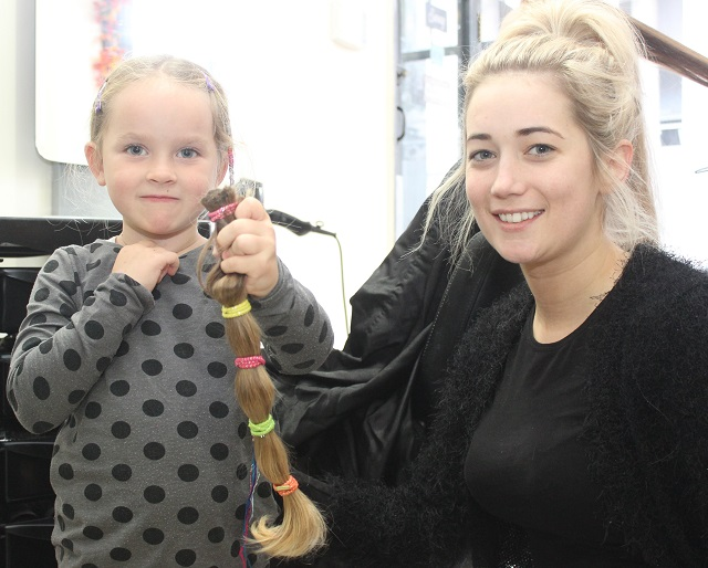 Kelly Hayes holds out her ponytail, with the hairdresser who cut it Joanne Lynch. Photo by Gavin O'Connor.