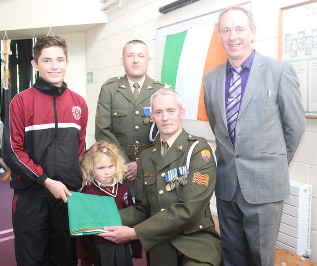 The oldest and the youngest pupils in Holy Family National School, Conor Commane and Lauren Hurley receive the tricolour from Sgt Chris Hore, with Gnr James Power and Principal Ed O'Brien. Photo by Gavin O'Connor.