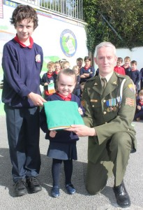 The oldest and the youngest pupils in Listellick National School, Jack O'Hare and Evie O'Donoghue receive the tricolour from Sgt Chris Hore. Photo by Gavin O'Connor.