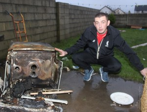 Jamie Norman, next to the dishwasher that caught fire in his house. Photo by Gavin O'Connor.