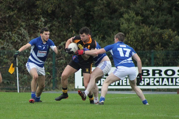 Shane Carroll, attempts to go passed, Laune rangers players, Ryan Keane and Chris Riordan.