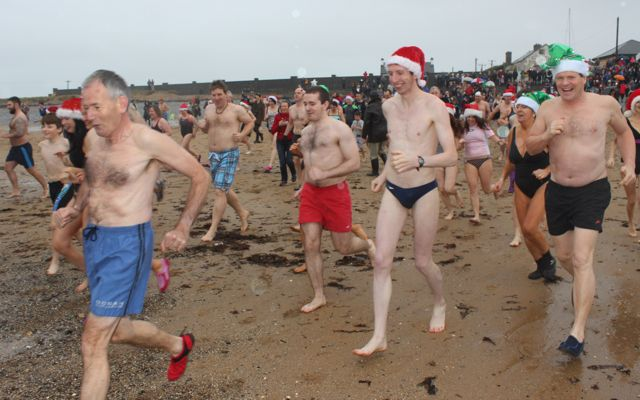 Happy swimmers making the first dash into the water for the Christmas Day swim in Fenit. Photo by Dermot Crean