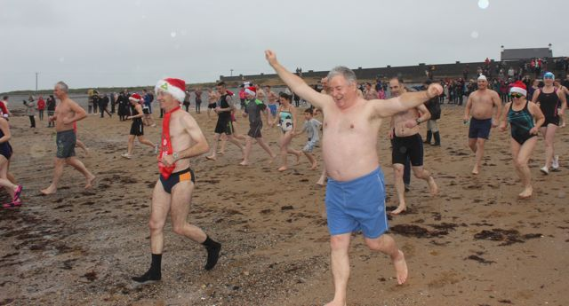 God bless their enthusiasm...swimmers dashing into the water for the Christmas Day swim in Fenit. Photo by Dermot Crean