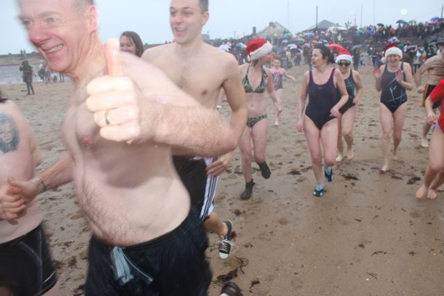 Tom Shea gives the thumbs-up making the dash into the water for the Christmas Day swim in Fenit. Photo by Dermot Crean