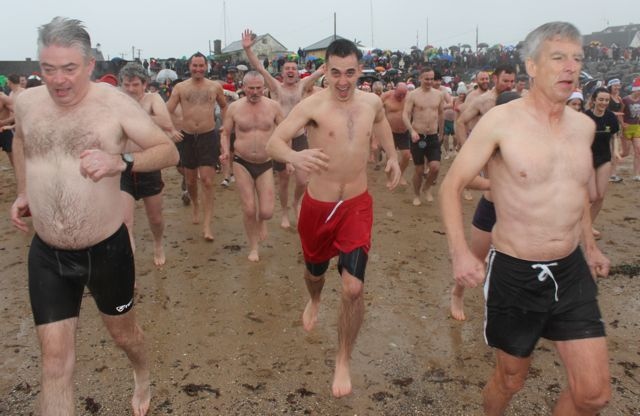 Different reactions on faces making the final dash towards the water for the Christmas Day swim in Fenit. Photo by Dermot Crean