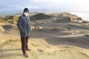 Banna resident, Pat Lawlor, stands over sand dunes that are being blown away by the wind. Photo by Gavin O'Connor.