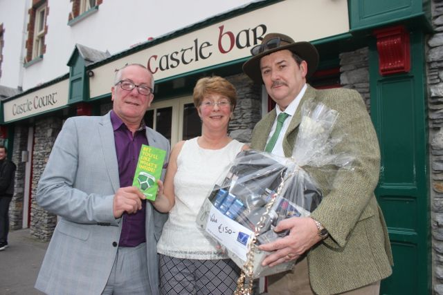 Sheila O'Sullivan presents the Best Dressed Man runner-up prize of a voucher for Paddy Power to Jeremiah Naughton (left) and the first prize to Vincent Power (right) at The Castle Bar on Wednesday. Photo by Dermot Crean