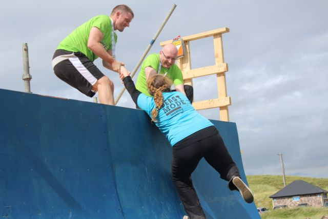 Anna O'Shea gets a helping hand from Dermot Gannon and Damien Moore at the end of the Banna Beast Challenge on Saturday. Photo by Dermot Crean