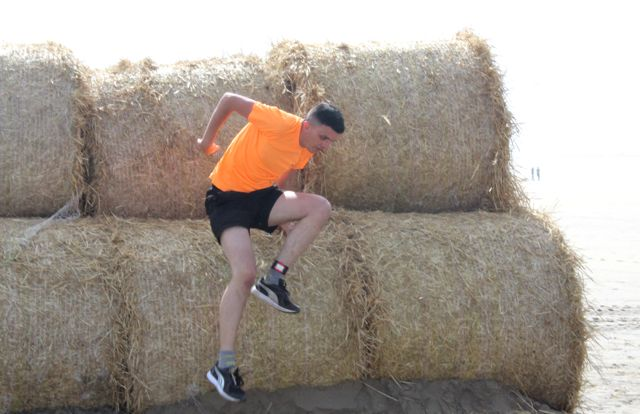 Over the bales at the Banna Beast Challenge on Saturday. Photo by Dermot Crean