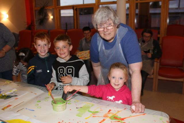 Catherine Pearson helps Oran Leen, Eoin Commane and Aoibhin Commane with their artistic endeavours at the Culture Night event at Baile Mhuire Day Care Centre in Balloonagh. Photo by Dermot Crean