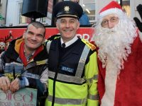 Kerry Garda Division Chief Superintendent Tom Myers with Billy Galvin and Santa at the Garda collection for Inspired Group on The Mall on Wednesday. Photo by Dermot Crean