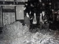 December 1973 find Tralee boys outside Baily's corner Tralee, where the pressure of water blew the manhole cover skyhigh during the flood, result of the heavy rain can be seen on the photograph due to the rain drops on the lens. LtoR. John McMahon, Jimmy Stack, Dan Healy, and Billy Brosnan.