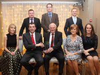 Declan Lovett (seated centre) accepts the Hall of Fame award from Chairman of Kilmoyley GAA Club Joe Walsh at the Kilmoyley GAA Social in Ballyroe Heights Hotel on Saturday night. Also included are seated; Noreen Lovett, Nora Lovett and Karen Daly. Back; John Nolan, Xavier Lovett and Tom Daley. Photo by Dermot Crean