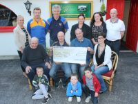 Alan Freeman (seated second from left) accepts his lotto winnings from Ballymacelligott GAA Club Chairman, Jeremiah Lynch at Glenduff Manor on Friday evening. Also included, back from left are; Noelle O'Brien, Padraig Laide, Mike Sweeney, Katie Leen, Paula Silles and Tony Silles. Seated; Tom Leen (President), and Laura Freeman. In front; Blake Leen, With James and Evan Freeman. Photo by Dermot Crean