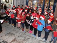 Principal Mary Connolly with pupils from Caherleaheen NS carol singing on The Mall on Friday. Photo by Dermot Crean