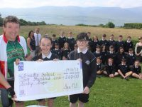 Tom Sheehy who undertakes fundraisers for Enable Ireland, accepts the cheque from sixth class pupils who gave up some of their confirmation money for the charity. Also included is Ms Buckley, Principal Peter Linehan and  Sharon Scanlon from Enable Ireland. Photo by Dermot Crean