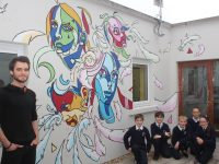 Artist Gabriel Galway with Caherleaheen NS pupils in front of his mural at the school. Photo by Dermot Crean