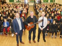 Musician John Spillane (centre) with Principal of Presentation Primary School John Hickey and Chairperson of the Parents Association Donal O'Callaghan in front of pupils before the concert in the school hall on Friday. Photo by Dermot Crean