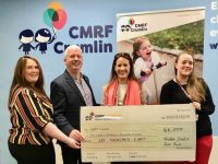 Martin Moore and Mags O'Regan Quillinan (second and third from left) present the proceeds of the Santa 5k run to representative off CMRF Crumlin.
