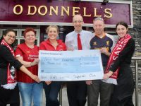 Regional Manager with the Irish Hearth Foundation, Anne Riordan (third from left), receives a cheque from Leo Byrne of the Kerry Liverpool Supporters Club (second from right). Also included were Sophie Byrne, Helen Moriarty, Manager of O'Donnells Ross Ahern and Clodagh Byrne. Photo by Dermot Crean