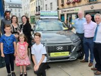 Denise O'Dowd collects the keys for her new Hyundai Kona from Suzanne Ennis, Marketing & Business Development Manager of Cara Credit Union. Also pictured is her husband Seamus and children Oísin, Muireann and Fionn, Noel O'Connor and Marcus O'Shea from Adams of Tralee and Derry Fleming of Cara Credit Union. Photo by Dermot Crean
