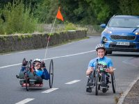Chris Slavin hand cycling with Cian Horgan on the Listowel-Tarbert leg of her Project Possible challenge. Photo by Poshey Aherne