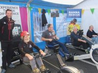 Mike Slattery of Kerry Mountain Rescue watches on as Jerry Christie, Shane Galvin, John O'Connor and Lesley O'Callaghan take part in the Rowathon on Saturday at Nolan's Garage. Photo by Dermot Crean