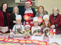 Minister Brendan Griffin launching the Ardfert NS Cookery Book with Marie O'Connell, Antonia Pierse , Principal Betty Stack, Peg Goggin and young budding chefs at the Ardfert Christmas Markets at Ardfert Community Centre on Sunday. Photo by Dermot Crean
