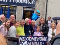 Jimmy Moran (centre) welcomed home by the Strand Road community.