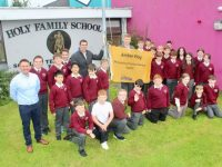 David Moran and Tommy Walsh with teacher Tommy Lyons, and Holy Family sixth class pupils at the raising of the Amber Flag at the school on Friday morning. Photo by Dermot Crean
